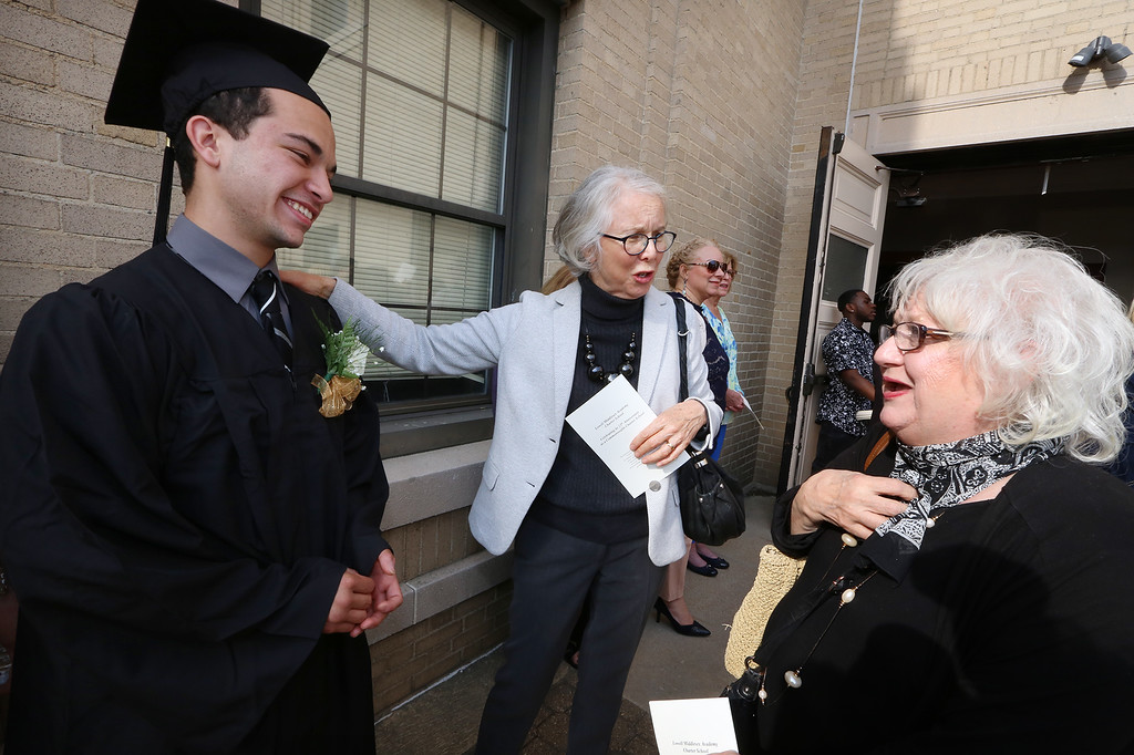 . Middlesex Charter graduation at MRT. From left, graduate Elijah O\'Neil of Lowell listens as his art teacher Engelie Blomerus of Lowell tells his grandmother Joanie O\'Neil Lowell about him. (SUN/Julia Malakie)