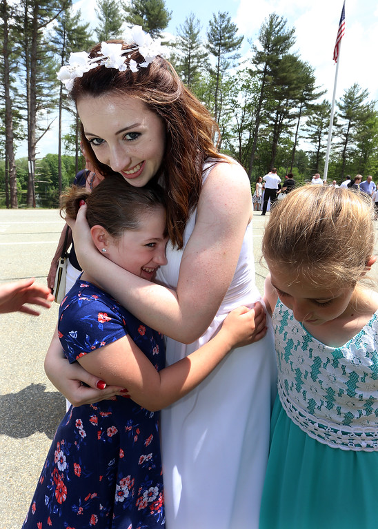 . Notre Dame Academy  graduation. Graduate Claire French of Nashua and Groton hugs her cousin Caroline Murphy, 8, of Dedham. At right is their cousin Julianna Kay, 8, of Uxbridge. (SUN/Julia Malakie)