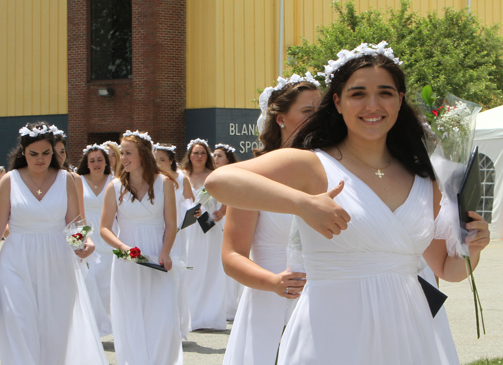 . Notre Dame Academy  graduation. Annmarie Kordish of Tyngsboro gives thumbs us as graduates walk to front steps for the group photo. (SUN/Julia Malakie)