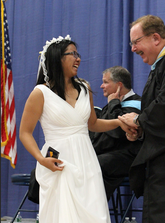 . Notre Dame Academy graduation. Annie Kelley of Lowell is greeted by science and math teacher John Versteeg after receiveing the Academic Excellence in Science award. (SUN/Julia Malakie)