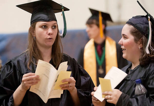 Record-Eagle/Douglas Tesner<br /> <br /> Kimberly Schaub, left, of Buckley, and Karianne Merritt chat and look over their programs before the NMC graduation at Traverse City Central High School.