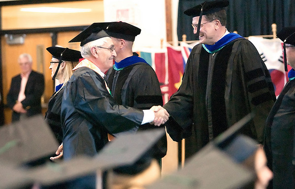 Record-Eagle/Douglas Tesner<br /> <br /> Luc Serriere, NMC's oldest graduate with honors, shakes hands with NMC Trustee Doug Bishop before receiving his diploma.
