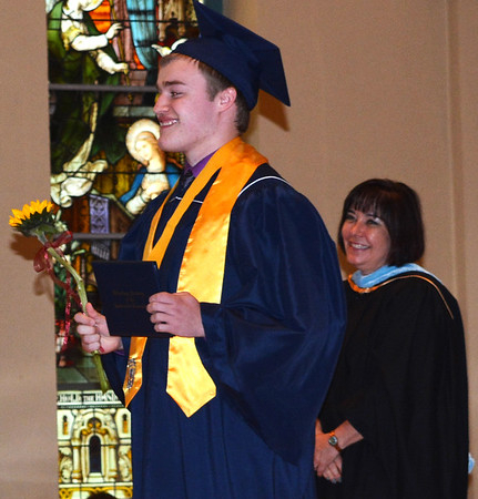 Diane Raver | The Herald-Tribune<br /> Benjamin Schebler smiles after receiving his diploma as President Diane Laake watches.