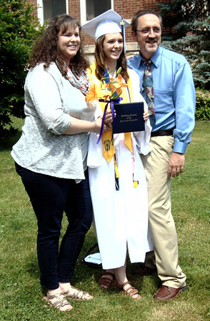 "Diane Raver | The Herald-Tribune<br /> Valedictorian Josie Wesseler poses for pictures with her parents, Carrie and Neil Wesseler, after the ceremony. Addressing her classmates in her speech, Josie said, ""These last four years have brought us failures we will always remember and successes we will never forget, especially our greatest success yet – graduation."