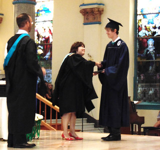 Diane Raver | The Herald-Tribune Samuel Fairchild receives his diploma and is congratulated by President Diane Laake as principal Brian McFee waits to hand the young man the class flower.