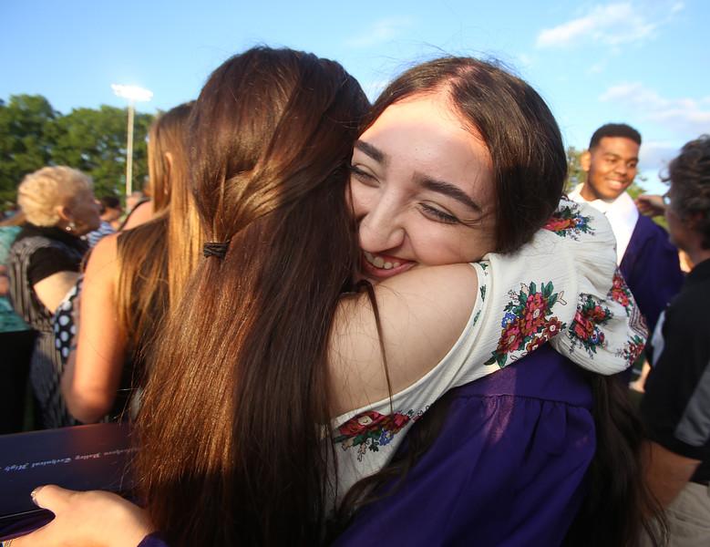 Shawsheen Tech graduation. Graduate Amber Matsas of Tewksbury, right, gets a hug from her friend Tori Browne of Billerica after graduation. (SUN/Julia Malakie)