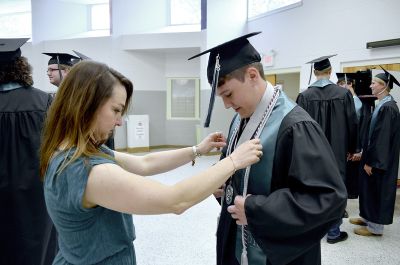 - Messenger photo by Kriss Nelson<br /> <br /> Bethany Rippentrop, Southeast Valley High School social studies instructor helps graduate Benjamin Peterson get ready for commencement on Sunday.
