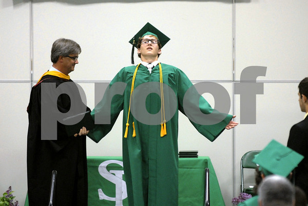 -Messenger photo by Hans Madsen<br /> <br /> Callaghan Coleman pretends to stretch Sunday afternoon after getting his diploma from Michael Johnson, at left, during the St. Edmond High School commencement exercises.