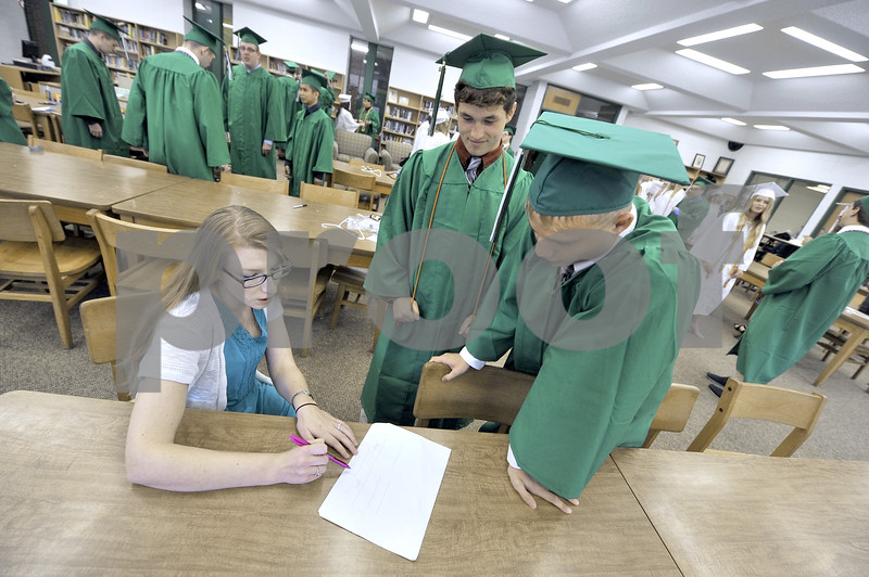 -Messenger photo by Hans Madsen<br /> <br /> St. Edmond Catholic Schools teacher Emily Van Egmond goes over the graduation plans with Cade Naughton and Jack Rasmussen, right. The paid had missed rehearsal due to a sports event.