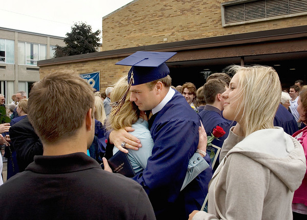 Record-Eagle/ Keith King<br /> Peter Rigan, 18, of Traverse City, hugs his mom, Patti Rigan, of Traverse City, while his cousin Sara Quackenbush, at right, of Dundee, stands near Sunday, June 6, 2010 at the conclusion of the Traverse City St. Francis High School graduation ceremony.