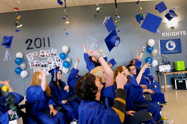 Record-Eagle/Jan-Michael Stump<br /> Traverse City College Preparatory Academy graduates toss their mortar boards in the air at the end of Friday's ceremony.