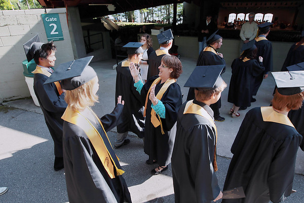 """Record-Eagle/Keith King<br /> Pat Bowen, Traverse City Central High School administrative assistant, gives high fives to students Sunday, June 3, 2012 as they proceed into Kresge Auditorium for the Traverse City Central High School commencement at the Interlochen Center for the Arts. """"Enjoy it,"""" Bowen said."""