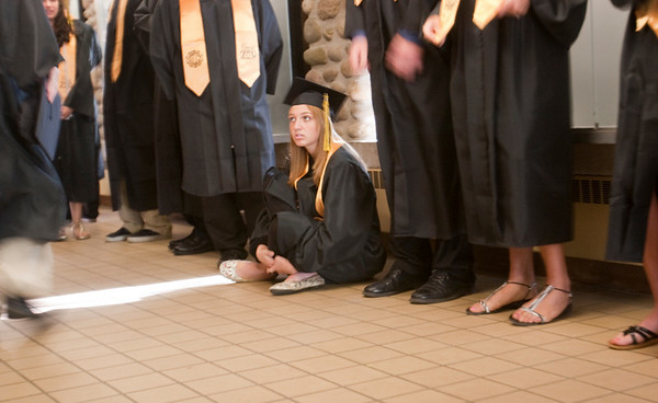 Record-Eagle/Douglas Tesner<br /> Lizzie Andriese takes a seat on the floor before the start of the commencement ceremony.