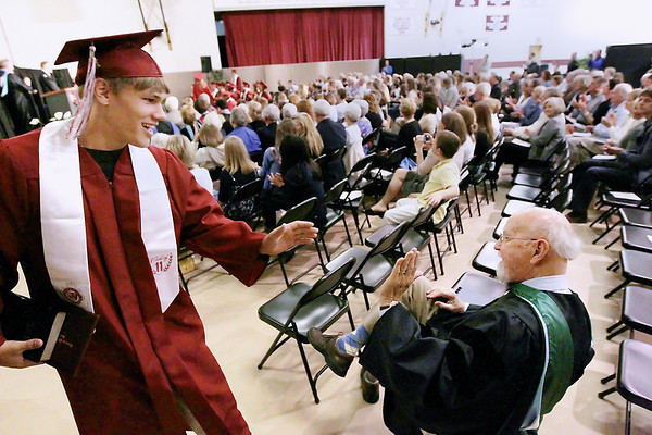Record-Eagle/Keith King<br /> Peter Mustard, left, exchanges a high five with Dr. K. Patrick Rode, who retired last year as Traverse City Christian School principal and administrator and who delivered this year's commencement address, Saturday, June 11, 2011 during the Traverse City Christian School graduation ceremony.