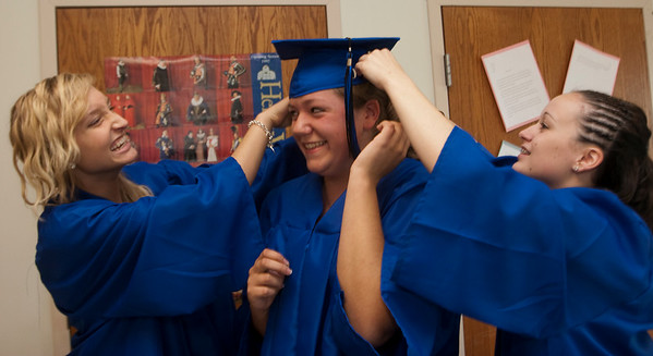 Record-Eagle/Douglas Tesner<br /> Samantha Walton and Meryah Martin help Emily Lardie put on her mortar board before taking part in their commencement ceremony at Traverse City College Preparatory Academy.  This year the school had a total of 14 graduating seniors.
