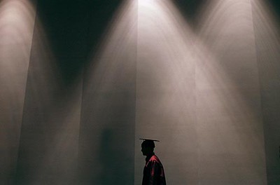 Record-Eagle/Tyler Sipe<br /> A Traverse City High graduating senior makes his way to the stage during Thursday evening's commencement at Milliken Auditorium. Nearly 50 students graduated from the high school