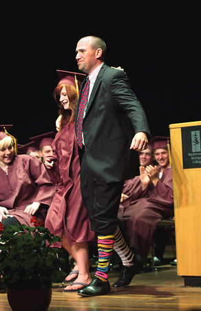 Record-Eagle/ Keith King<br /> Lance Morgan Jr., principal of Traverse City High School, walks with senior Hayley Ralston Friday, June 11, 2010 during the Traverse City High School graduation ceremony at Milliken Auditorium. Ralston was known to make fun of Morgan's fashion sense, particularly his socks, so Morgan made a deal with Ralston that if she graduated, he would wear whatever socks she picked out for him during the graduation ceremony.