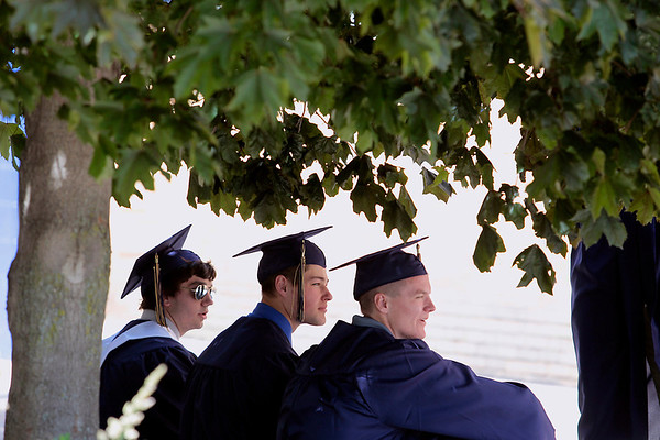 Record-Eagle/Jan-Michael Stump<br /> From left, Hayden Wilson, Zack Swaffer and Marc Stein sit in the shade before the start ofTraverse City St. Francis' graduation Sunday.
