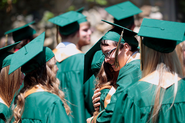 Record-Eagle/Jan-Michael Stump<br /> Alyssa Crough, left, and Joey Vanderbosch hug before the start of the Traverse City West commencement Sunday at Interlochen Center for the Arts.