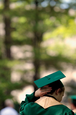 Record-Eagle/Jan-Michael Stump<br /> Lucas Cozart adjusts his mortar board before the start of Traverse City West's commencement Sunday at Interlochen Center for the Arts.
