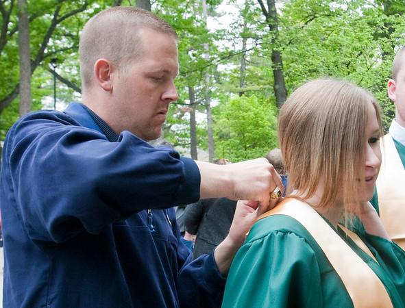 Record-Eagle/Douglas Tesner<br /> Courtney Winnowiecki has her stole pinned in place by a Jostens representative.
