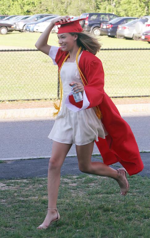 . Tyngsboro High graduation. Emma Strong runs to join friends for a photo. (SUN/Julia Malakie)