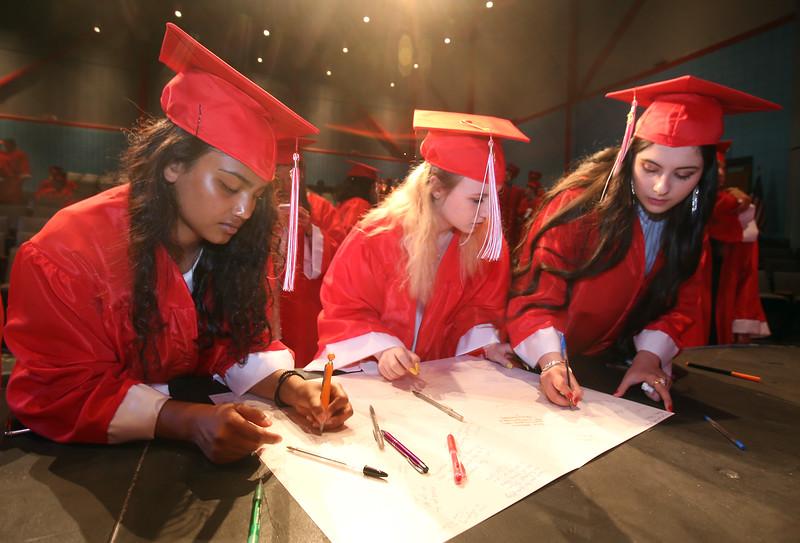 From left, Suzanna Samuel, FaithMary Harding, and Seleen Al Horani sign cards for class advisors before Tyngsboro High graduation. (SUN/Julia Malakie)