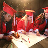 From left, Suzanna Samuel, FaithMary Harding, and Seleen Al Horani sign cards for class advisors before Tyngsboro High graduation. (SUN/Julia Malakie)