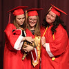 From left, Lizzie Storry, Abby McIsaac and Emily Holzman have a friend take their picture with Toby the Christmas Tiger, a theatre mascot, on the auditorium stage before. Tyngsboro High graduation. (SUN/Julia Malakie)