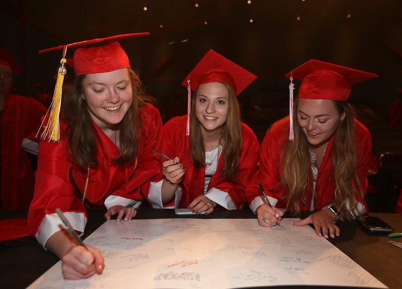 Tyngsboro High graduation. From left, Terryn Fraser-Mines, Lizzie Storry and Amanda Pare sign cards for the senior class advisors before graduation. (SUN/Julia Malakie)