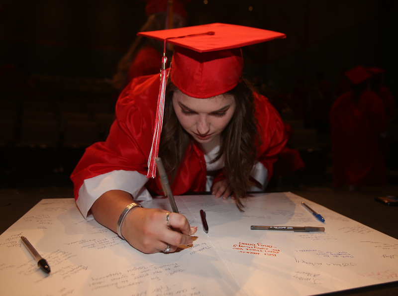 Kaleigh Lessieur signs cards for class advisors before Tyngsboro High graduation. (SUN/Julia Malakie)