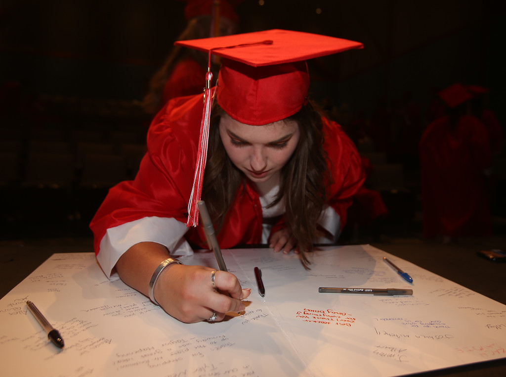 . Kaleigh Lessieur signs cards for class advisors before Tyngsboro High graduation. (SUN/Julia Malakie)