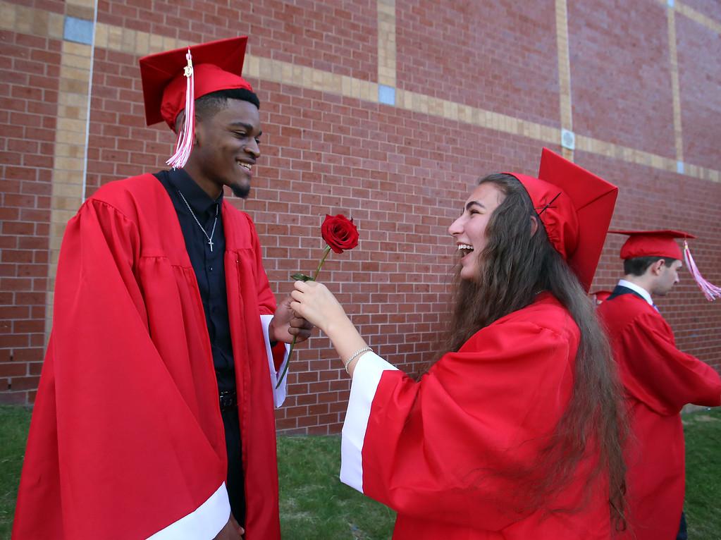 . Tyngsboro High graduation. Taylor Hapenny, right, shows Elcharis Kamuanga, her rose. (SUN/Julia Malakie)