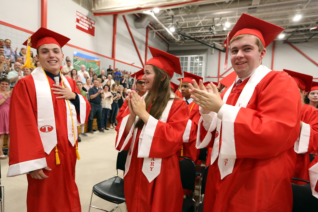 . Tyngsboro High graduation. Class president Corey O\'Neill, left, gets a standing ovation after his speech, in which he left the podium for the last part and spoke from memory. At right are class secretary Sydney McCarty and vice president Christopher Fournier. (SUN/Julia Malakie)