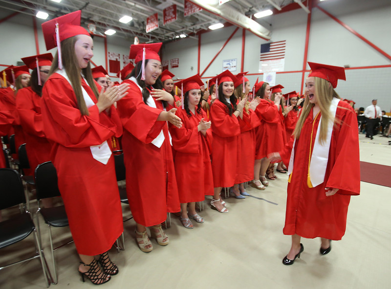Tyngsboro High School graduation, at the high school. Salutatorian/Vice President Catherine Riley returns to her seat after giving her address. At left are Sarah McCarty and Emerald Robertson. (SUN/Julia Malakie)