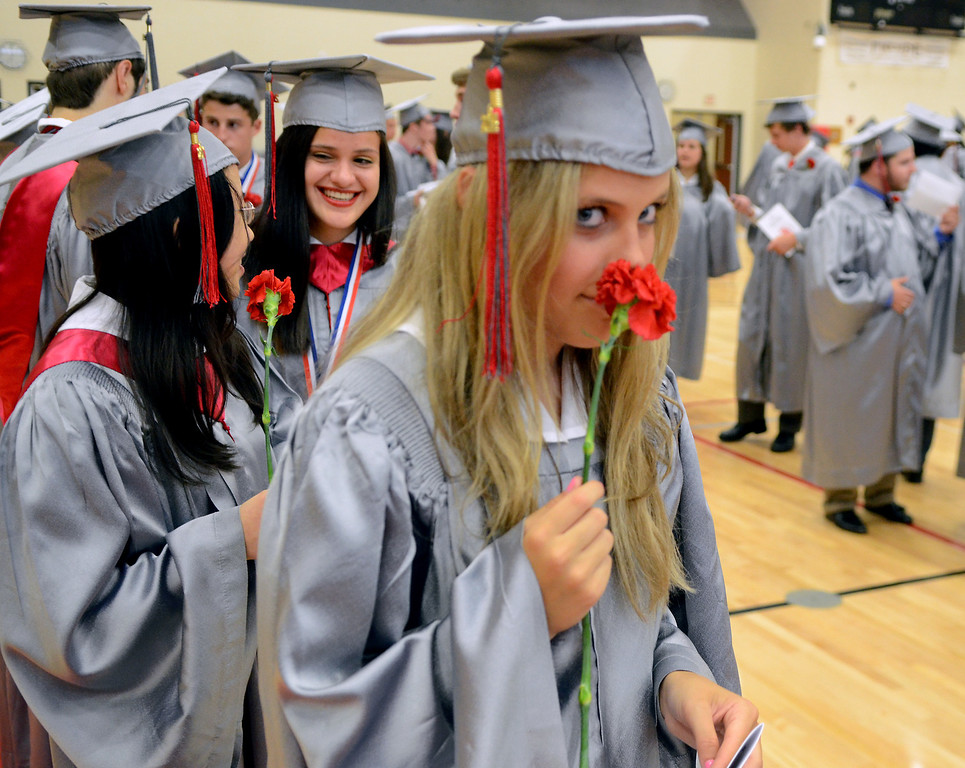 . Upper Dublin High School Class of 2014 member Anna Trentini smells her carnation as the class  lines up in the gym before the start of  their Commencement Ceremony at the school on Tuesday evening June 10,2014. Photo by Mark C Psoras/The Reporter