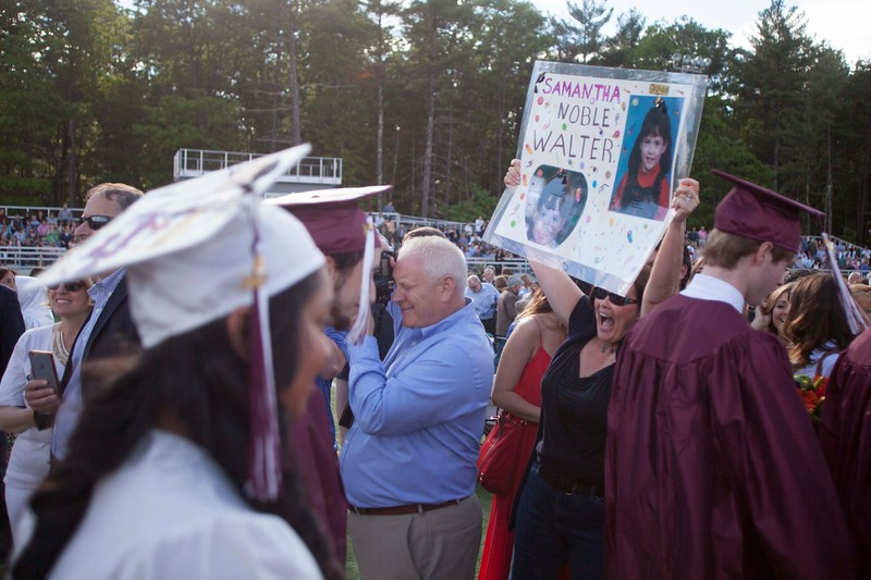 Judy Giliberti cheers and holds a sign for Samantha Walter, her goddaughter, during Westford Academy's graduation on Friday. Lowell Sun/Chris Lisinski