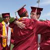 Westford Academy graduation. Alex Blais, right, hugs class secretary Carter Purple after getting his diploma. At left is class president Viraj Jayaraman.  SUN/Julia Malakie