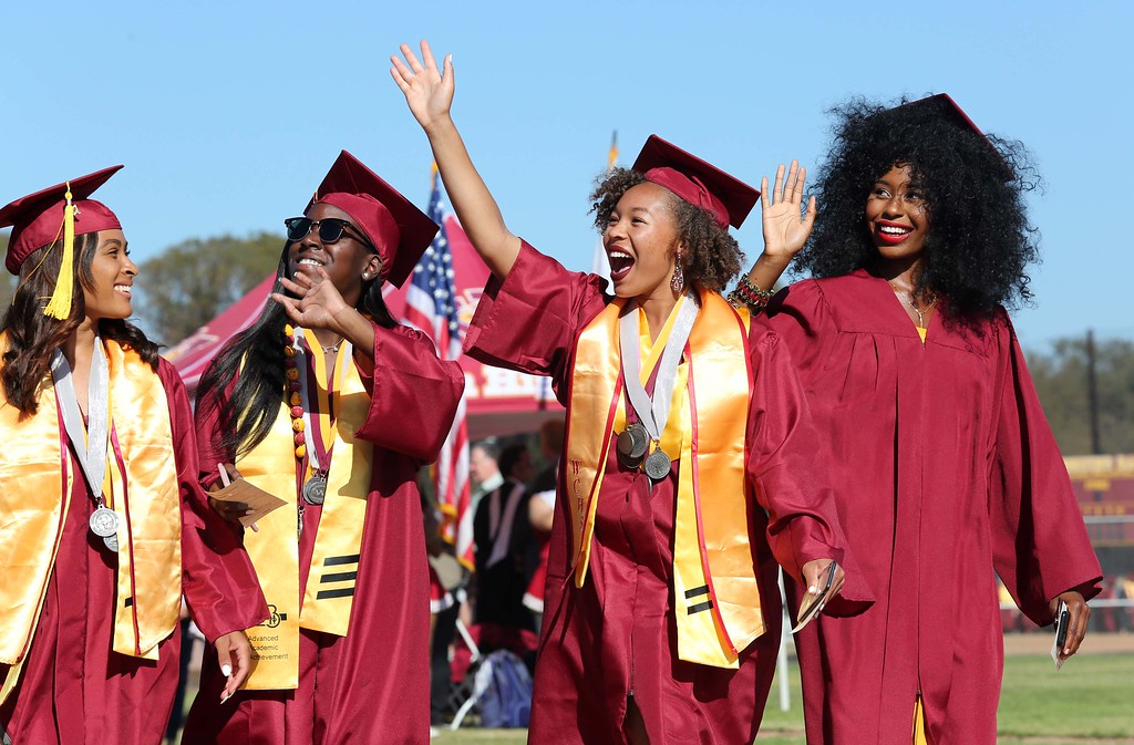 . June 15, 2017-Photo by Tracey Roman/for the Press-Telegram Long Beach Wilson Seniors wave to the crowd as they walk in their graduation ceremony Thursday evening.