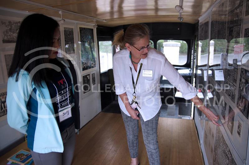 Kathrine Schlageck shows GraficoMovil in Manhattan, a mobile printmaking studio/gallery, created by Artemio Rodriguez, to Biak Sung, a student of Kansas City Kansas Community College  (Saya Kakim  Collegian Media Group)