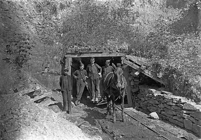 """Drift Mouth, San Lick Mine, near Grafton, W. Va. Bank Boss in centre: driver on his right: trapper boy outside. Alfred, about 14. He trapped several years during vacation: said he is going to school this year: asked if it were because school is more fun he said. """"This yere hain't no fun!"""". Location: Grafton, West Virginia."""