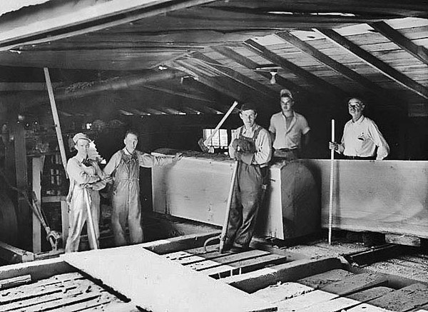 Workers at the Woodyard Lumber Company on West Main Street in Grafton, West Virginia. The photograph was taken in the shed as a log is being cut into boards. L to R: Ralph Woodyard (son of owner), Edwin Woodyard (son of owner), unidentified worker, Bill Woodyard (son of owner), and W. A. Woodyard, owner. The lumber company was owned and operated by the Woodyard family until 1990. The property was sold and the building was razed in 1992.