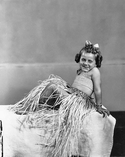A smiling young girl is wearing a grass skirt while posing for the photographer.