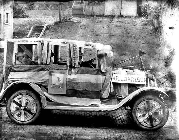 Car decorated with W.R. Loar & Son signs on it, as well as advertisements for Kodak film, perhaps for a parade. Grafton, WV 1926.