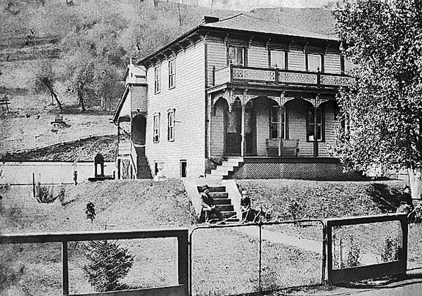 'Second home of M. H. Dent family - facing Barrett St. in Grafton, W. Va. - directly behind and above first home. Judge Dent & Herbert on steps - Mrs. Dent & Carrie under tree. Probably taken around 1890-95. He later built a large brick house on Washington Street uphill from Post Office.