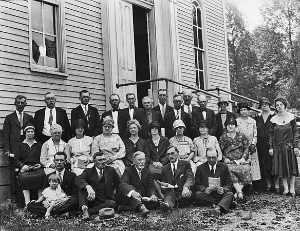 'Second Row, Left to Right, Fourth from Left: Margaret Leach Felton (Mrs. George C. Felton). First Row seated on ground, Left to Right: Tracey Felton holding unidentified boy; George C. Felton.'