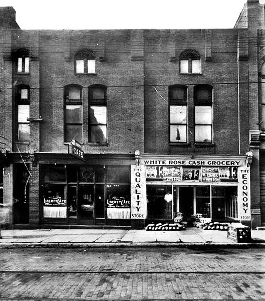 1926 - Exterior view of the Liberty Cafe and White Rose Cash Grocery Store in the Cohen Building in Grafton, W. Va.