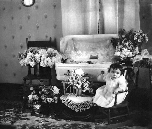 An unidentified child lays in a coffin while another child sits in a rocking chair near the casket, Grafton, WV