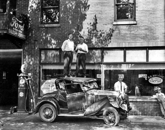 Two Men Standing Atop a Wrecked Car in front of B.B. Bryant Ford Dealership in Grafton, W. Va.