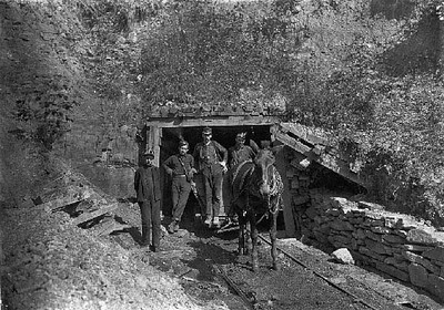 "Drift Mouth, San Lick Mine, near Grafton, W. Va. Bank Boss in centre: driver on his right: trapper boy outside. Alfred, about 14. He trapped several years during vacation: said he is going to school this year: asked if it were because school is more fun he said. ""This yere hain't no fun!"". Location: Grafton, West Virginia. Date: 1908 October. Photos of child labor by Lewis Hine."